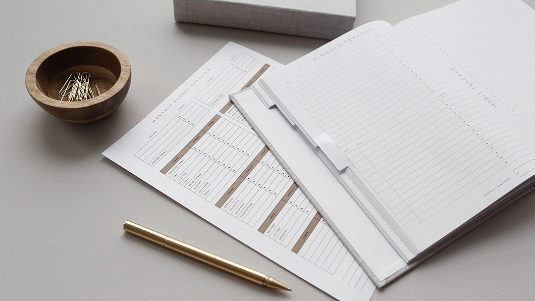 close up of financial paperwork on a white desk with a gold pen and a bowl of paper clips