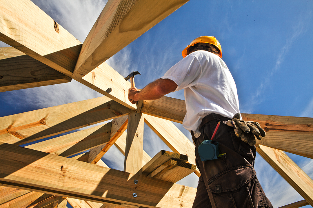 Carpenter in hard hat works on a construction site