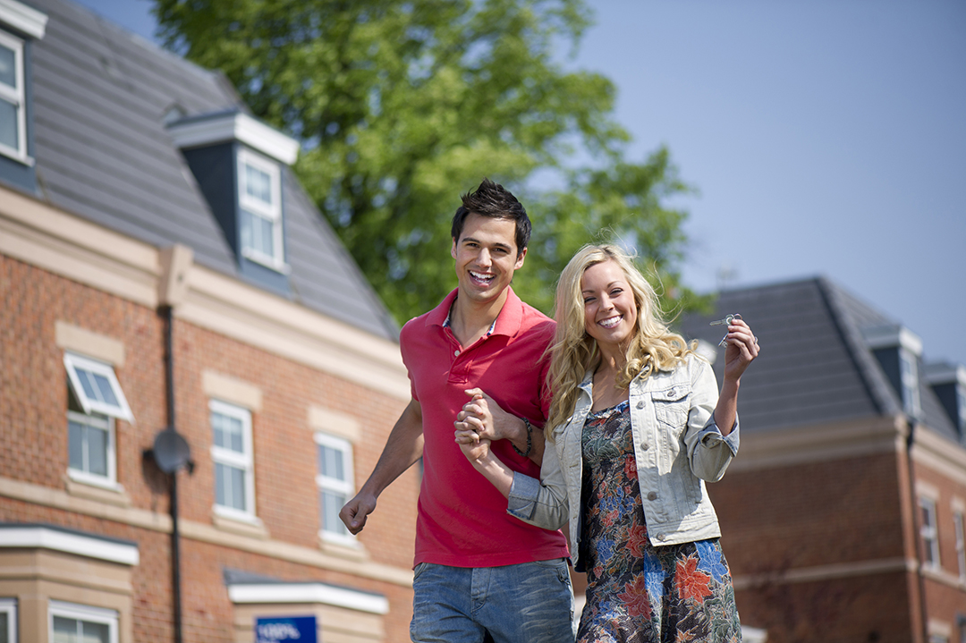 Young couple standing in front of a sold sign holding the keys to their new home.